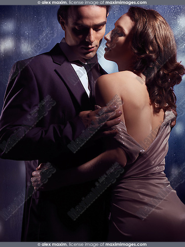 Artistic sensual photo of a couple standing in front of a window on a rainy night. Man in suit taking off young woman's dress.