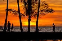 A colorful sunset-lit sky silhouettes a family amidst palm trees at 'Anaeho'omalu Bay and Waikola Beach, Big Island.