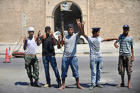 Young men hold guns and guard a checkpoint on a street in Tripoli. As soon as the rebel offensive gained steam, the population of Tripoli took up arms and took to the streets to defend their neighbourhoods and take on Gaddafi loyalists. After a six month revolution, rebel forces finally managed to break into Tripoli and have taken control of Bab al-Aziziyah, Col Gaddafi's compound and residence. Few remain that are loyal to Gaddafi in the city; it is seeming that the 42 year regime has come to an end. Gaddafi is currently on the run.