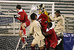 13 November 2009: NC State goalkeeper Christopher Widman (in yellow) punches the ball clear in traffic. The North Carolina State University Wolfpack defeated the Boston College Eagles 1-0 at WakeMed Stadium in Cary, North Carolina in an Atlantic Coast Conference Men's Soccer Tournament Semifinal game.