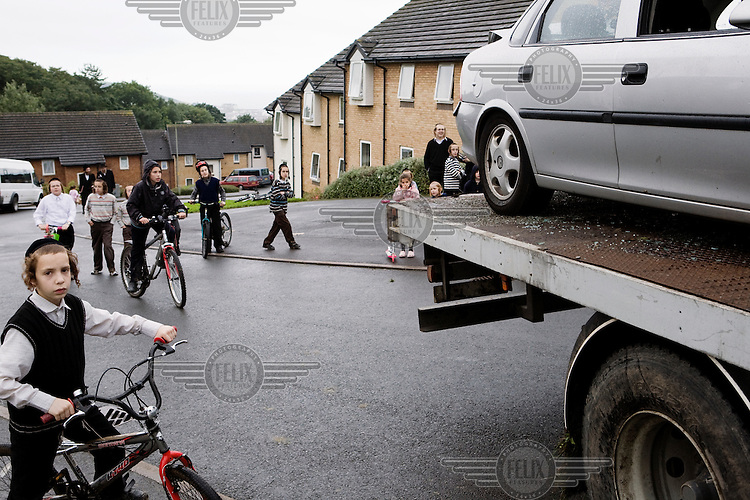 Hasidic children ride around on bicycles as a lorry takes away a damaged car at the campus. Hasidic families stay in Pentre Jane Morgan university accommodation when they holiday in Aberystwyth. Every other day, bread, milk and other supplies are brought from Kosher shops in London and resold from one of the rented houses on the campus.