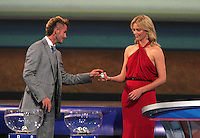 David Beckham hands a ball to Charlize Theron during the FIFA Final Draw for the FIFA World Cup 2010 South Africa held at the Cape Town International Convention Centre (CTICC) on December 4, 2009.