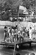 Middlefield, CT. August 1st and 2nd 1970.<br /> Powder Ridge Festival in Middlefield. Naked people on a raft.<br /> The American Flag was hanged upside down as a sign of protest against the American Government for sending young men to the war agains their will.<br /> The Powder Ridge Rock Festival was scheduled to be held July 31, August 1 and August 2, 1970 at Powder Ridge Ski Area in Middlefield, Connecticut. A legal injunction forced the event to be canceled, keeping the musicians away; but a crowd of 30,000 attendees arrived anyway, to find no food, no entertainment, no adequate plumbing, and at least seventy drug dealers.
