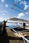 Workers guide a solar panel being lowered by a crane inside the Minamisoma Agri-Solar Park in Minamisoma, Fukushima, Japan on 10 Feb 2013 ..Photographer: Robert Gilhooly