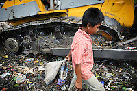 Taupik, 14, walking alongside a bulldozer on the 'Trash mountain', Makassar, Sulawesi, Indonesia.  Many of the pickers follow the bulldozers as they move newly dumped waste, uncovering plastic and metal for recycling in the process.