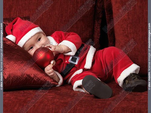 Six month old baby boy in Santa Christmas costume holding a red bauble in his hand