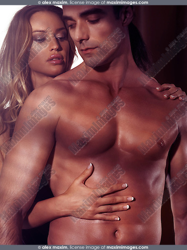 Artistic sensual portrait of a sexy young couple, woman touching man bare torso with her hand