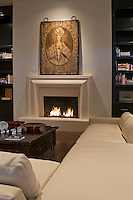 Living room fireplace is seen in contemporary home with white sectional couch