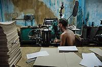 A Cuban master printer operating a printing machine in the state print shop, Santiago de Cuba, Cuba, 4 August 2008.