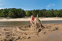 Eight years old girl building sandcastle on Kauksi beach. Lake peipsi in Estonia.