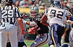 Oakland Raiders vs. San Diego Chargers at Oakland Alameda County Coliseum Sunday, September 3, 2000.  Raiders beat Chargers  9-6.  San Diego Chargers defensive end Darren Mickell (92) moves in on Oakland Raiders quarterback Rich Gannon (12).