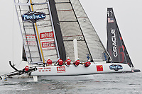 PORTUGAL, Cascais. 6th August 2011. America's Cup World Series. Day 1. CHINA TEAM, with ORACLE Racing Coutts in the background.