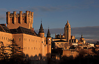 The Alcazar, 12-16th centuries, Segovia, Castile and Leon, Spain. The current Alcazar was begun by King Alfonso VIII (1155-1214) and his wife Eleanor of England (1162-1214), and rebuilt 1258. Juan (John) II (1405-54) added the Gothic style Great Tower. Philip II (1527-98) modified the roofs with slate spires in Northern European style. The Alcazar was subsequently a state prison until it became the Royal Artillery School, 1762. It was damaged by fire, 1862 and restored, 1882, becoming a Military College, 1896. Segovia Cathedral, (Catedral de Segovia, Catedral de Santa Maria), 1525-77, by Juan Gil de Hontanon (1480-1526), and continued by his son Rodrigo Gil de Hontanon (1500-1577), visible in the distance. Picture by Manuel Cohen