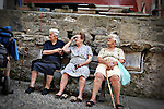 Photo of three old women sitting on a bench in Vernazza, Italy.