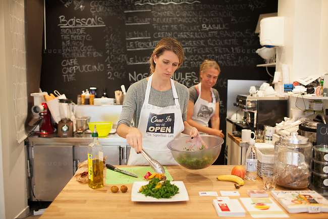 Kristen Beddard, 29, of The Kale Project, prepares a kale salad at The Superfoods Cafe, while owner Elke Seyser looks on, in Paris, France.  Kevin German / Luceo