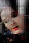 woman with red lips and white face looking through corrugated glass