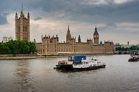 Dramatic cloudy day view of ship traffic and Parliament on the River Thames and in London, England.