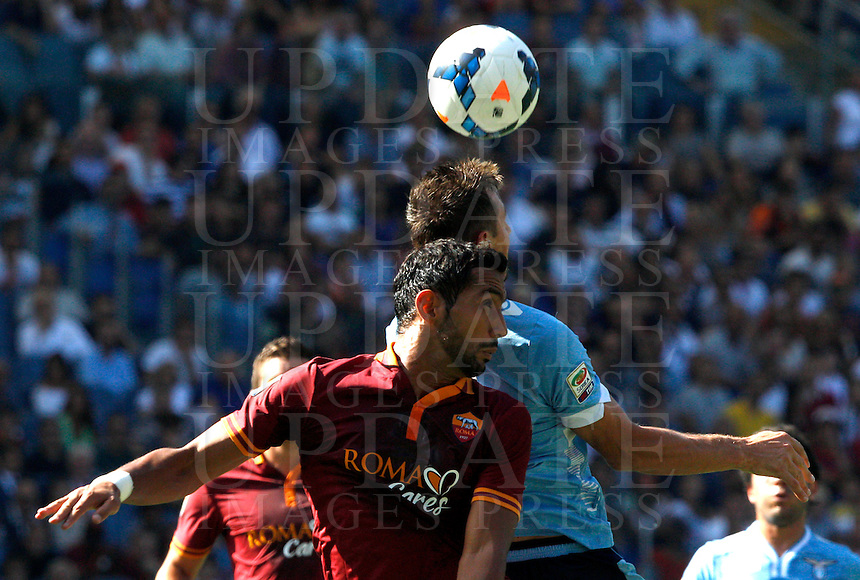 Calcio, Serie A: Roma vs Lazio. Roma, stadio Olimpico, 22 settembre 2013.<br /> AS Roma defender Mehdi Benatia, of France, foreground, and Lazio forward Miroslav Klose, of Germany, jump for the ball during the Italian Serie A football match between AS Roma and Lazio, at Rome's Olympic stadium, 22 September 2013.<br /> UPDATE IMAGES PRESS/Riccardo De Luca