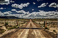 A cattle guard on Sandoval County Road 279 in the Rio Puerco Valley leading to the Empedrado Wildernas Study Area with Cerro Parido in the background.