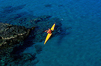 A man ocean kayaking in the blue waters of the coast of The Big Island of Hawaii.