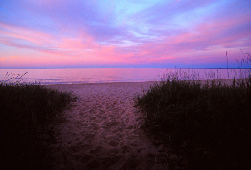 A PATH LEADS TO A DESERTED SANDY LAKE SUPERIOR BEACH AT DUSK IN MARQUETTE MICHIGAN WITH FOOTPRINTS.