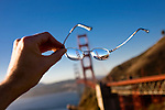 The Golden Gate Bridge is reflected in a pair of eyeglasses on a sunny day.