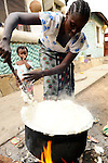 A woman in Likoni, Kenya at her home cooking a mid day porridge to sell to workers for lunch.