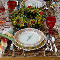 Detail of a table laid with bowls of soup set on rustic table mats and surrounded by red glassware and a floral centrepiece