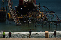 People watch while a crane works to remove remnants of the Jet Star roller coaster that had been left in the ocean after Superstorm Sandy hit Seaside Heights last year, in New Jersey  May 14, 2013, Photo by Eduardo Munoz Alvarez / VIEWpress.