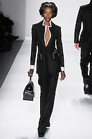 Model walks runway in a black loro piana cashmere/silk trouser suit w/ivory silk gazar upturned peak lapel+cuff and ivory hand-top-stitching, from the Zang Toi Fall 2012 &quot;Glamour At Gstaad&quot; collection, during Mercedes-Benz Fashion Week New York Fall 2012 at Lincoln Center.