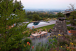 The view of the Willamette Valley and Coast range in the distance from the vantage point of the hillside, drought tolerant garden.  The swimming pool, dining area and outdoor fireplace are visible.