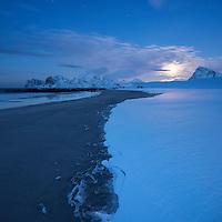Moon rises over snow covered Storsandnes beach in winter, Flakstadøy, Lofoten Islands, Norway