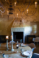 The dining room is lit by candlelight from a large chandelier above the rustic wooden table that contrasts with the Eames dining chairs