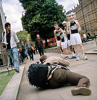 UK. London. From a story on Abingdon Street Gardens, a small patch of land, often referred to as College Green, that lies next to The Houses of Parliament in Westminster. It is a place where the media and the politicians come face to face. Interviews are held, photo shoots are set up and bewildered tourists stroll by..Photo shows a photographer working for Oxfam on the day Gordon Brown succeeded Tony Blair as Britain's Prime Minister..Photo©Steve Forrest/Workers Photos