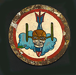 'Noseart' found near Port Moresby, Papua New Guinea.  //  A World War 2 USAAF airman camped near Durand's Strip on the outskirts of Port Moresby in the 1940s painted this 'skull in a flight cap' over a finned bomb on an inspection cover (~15cm diameter) from an airplane at his base. The original was found in a campsite near Durand's Strip 19YY, upside-down and covered in ashes from a recent grassfire in the kunai-grass swards covering the Port Moresby hills.  The mud-covered outer ring shows traces of gold/yellow paint.  Durand's was used by the 3rd, 38th and 345th Bomb Groups, and the 49th Fighter Group from 1942-44. //Eric Lindgren//