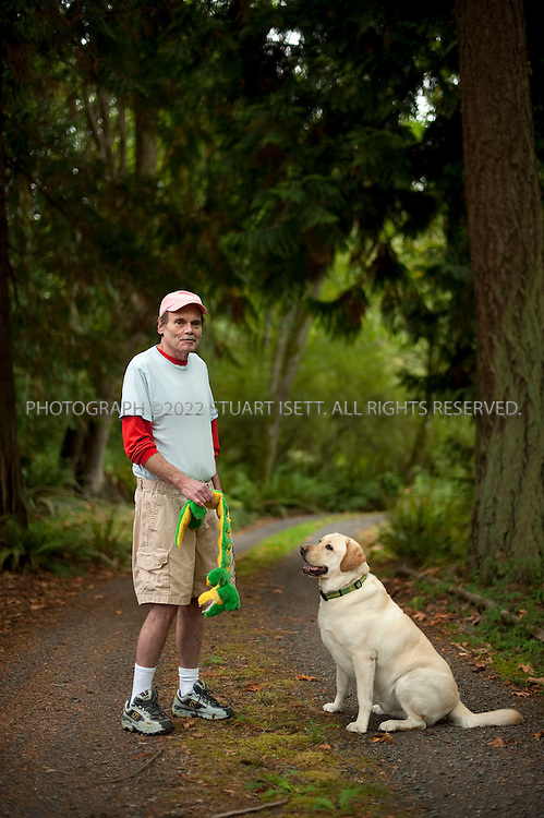 9/24/2009--Clinton, WA..Writer Pete Dexter, born 1943, posing in the woods near his home (with his dog 'Henry') on Whidbey Island, WASH. Dexter was the recipient of the 1988 National Book Award for Fiction for his novel Paris Trout. ..©2009 Stuart Isett. All rights reserved.
