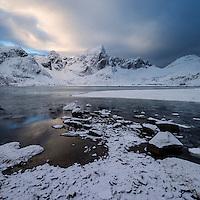 Stortind mountain peak rises over winter coastline at Flakstadpollen, Flakstadøy, Lofoten Islands, Norway