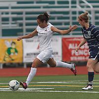 Boston Aztec forward Sonia Basma (8) crosses the ball.  In a Women's Premier Soccer League (WPSL) match, Boston Aztec (white) defeated Seacoast United Phantoms (blue), 3-0, at North Reading High School Stadium on Arthur J. Kenney Athletic Field on on June 25, 2013.