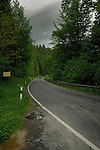 Car driving along country lane through forested area under cloudy leaden sky, Dammbach, Aschaffenburg district, Germany.