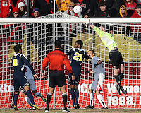 Zac McMath #1of the University of Maryland knocks the ball away from Latif Alashe #21 of the University of Michigan during an NCAA quarter-final match at Ludwig Field, University of Maryland, College Park, Maryland on December 4 2010.Michigan won 3-2 AET.