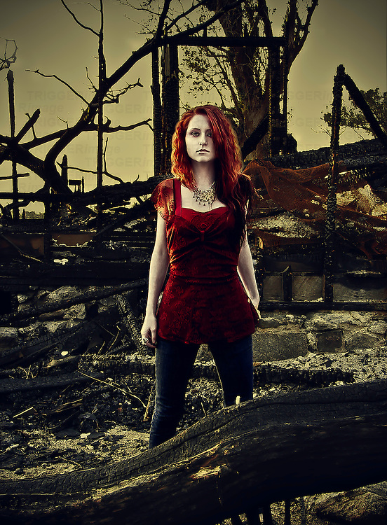 A young woman standing in the burn out ruins of a house