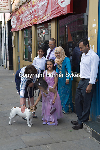 Muslim family London, children,  young girl being encouraged to touch a dog belonging to a white woman. They are happy and smiling. She has never done this before.