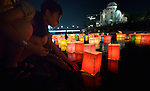A girl sets a floating candle lantern on the river on August 6, 2015, in Hiroshima, Japan. The lanterns, thousands of which were launched on the 70th anniversary of the atomic bombing of the city, carried handmade messages and drawings, conveying each person's prayers for peace and comfort for the victims of the violence. In the background are the ruins of a building damaged by the bomb and now converted into a peace memorial.