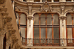 The balcony and windows of a covered arcade in Turin, Italy