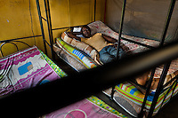 Eritrean immigrants, heading to the southern U.S. border, lie on the bed in the detention center in Metetí, Darién, Panama, 31 January 2015.