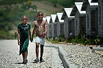 """Two girls walk along a street in a model resettlement village constructed by the Lutheran World Federation in Gressier, Haiti. The settlement houses 150 families who were left homeless by the 2010 earthquake, and represents an intentional effort to """"build back better,"""" creating a sustainable and democratic community."""