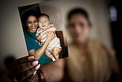 Surrogate mother for first western couple, Rabina Mondal (31) shows the photograph of Dr. Nayna Patel and Brady Kim who had delivered on February 2nd 2007 at the Akanksha Infertility Centre &amp; IVF Centre in Anand, Gujarat, India. Rabina  now mentors surrogate mothers and houses women throughout their pregnancy.