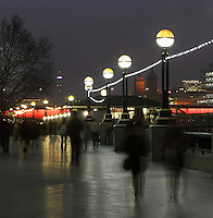 Banks of Thames with pedestrians, Millenium bridge in red in the distance, London, UK. Picture by Manuel Cohen