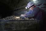 A miner loads ore in a cart deep under Cerro Rico in Potosi, Bolivia. The mine produces silver and other metals.