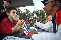Stanford, Ca - October 8, 2016: Eddie Hart, track Olympian, shows his gold medal to a fan before the Stanford vs. Washington State game Saturday night at Stanford Stadium. <br /> <br /> Washington State won 42-16.
